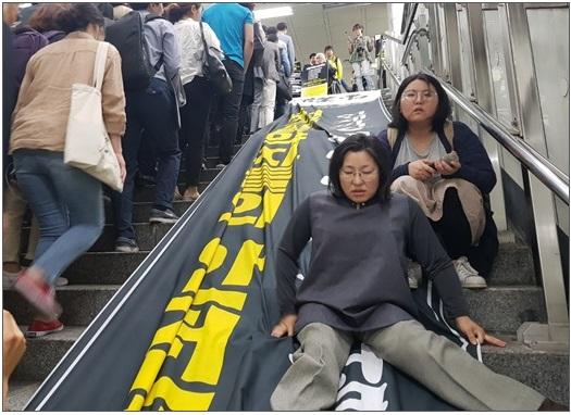 김광이 상상행동장애와여성 마실 대표가 23일 서울 광화문역 계단을 기어 오르고 있는 모습